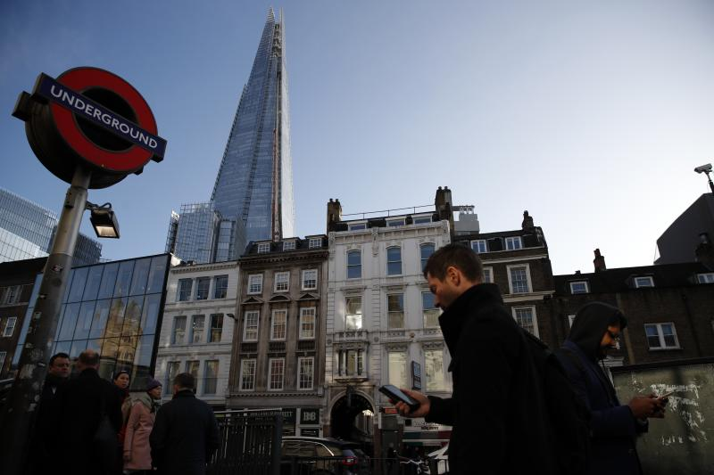 Commuters use the London underground, Wednesday, Dec. 11, 2019, backdropped by The Shard building. Britain will go to the polls tomorrow Dec. 12, to vote in a pre-Christmas general election. (AP Photo/Thanassis Stavrakis)