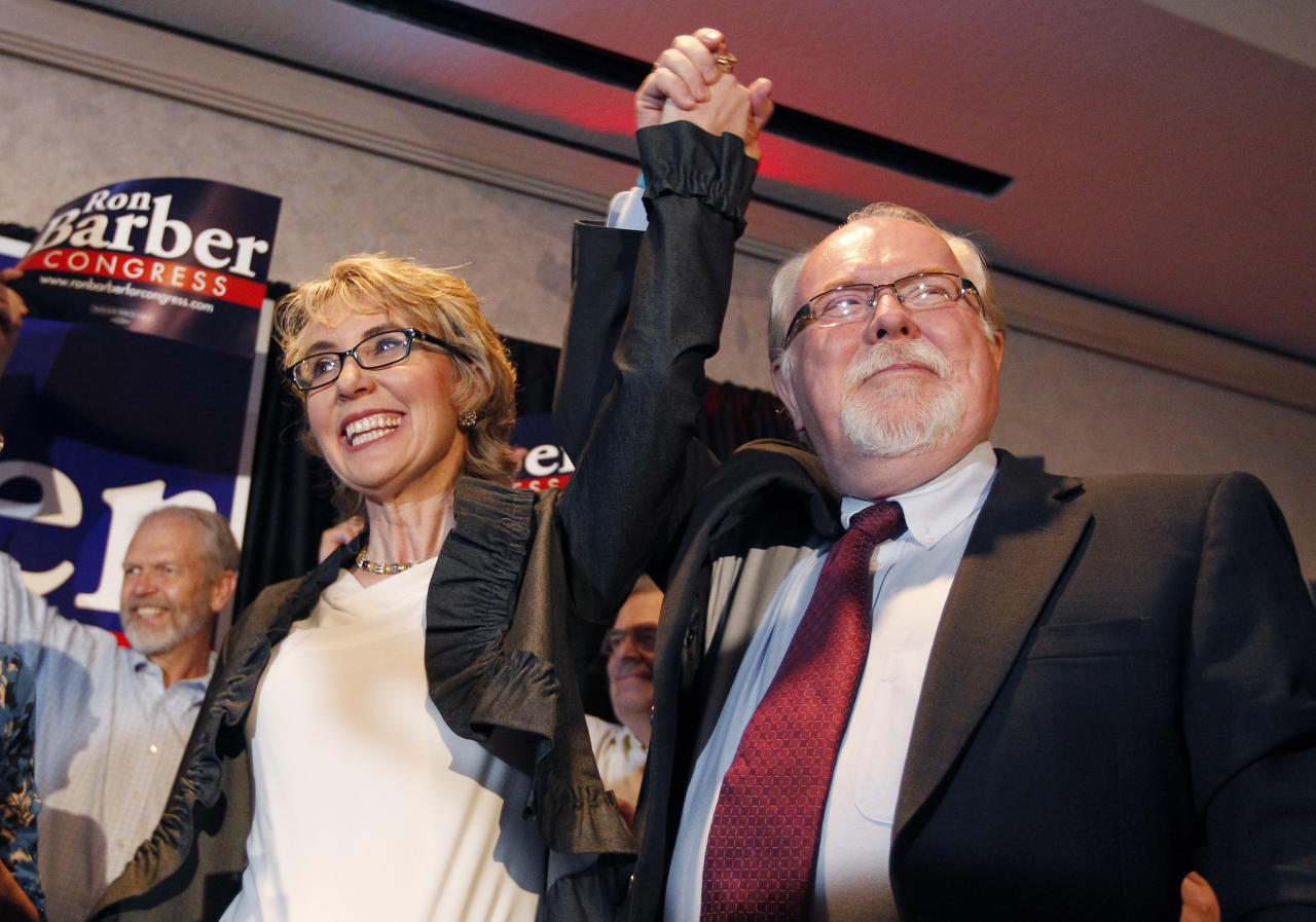 In an election to fill former Rep. Gabrielle Giffords, left, D-Ariz., congressional seat, Democratic candidate Ron Barber, right, celebrates a victory with Giffords and supporters at a post election event, Tuesday, June 12, 2012, in Tucson, Ariz. Gabrielle Giffords' former district director, in a special election for the seat Giffords left in January to focus on her recovery from a gunshot wound to her head during a gunman's shooting spree a year earlier.(AP Photo/Ross D. Franklin, pool)