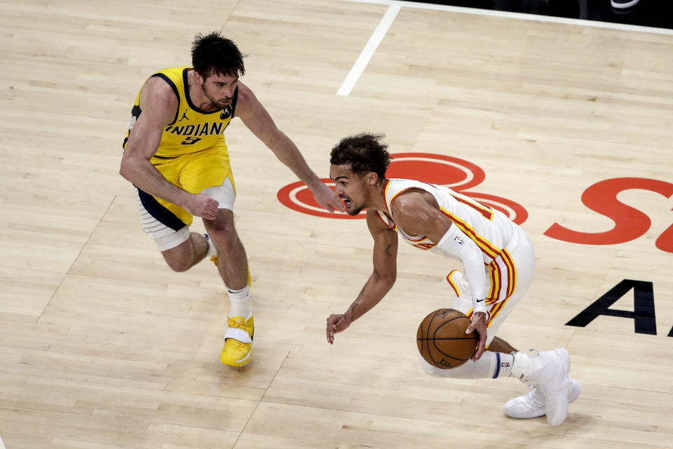 Atlanta Hawks guard Trae Young, right, drives to the basket around Indiana Pacers guard T.J. McConnel, left, during the second quarter of an NBA basketball game Saturday, Feb. 13, 2021, in Atlanta. (AP Photo/Butch Dill)