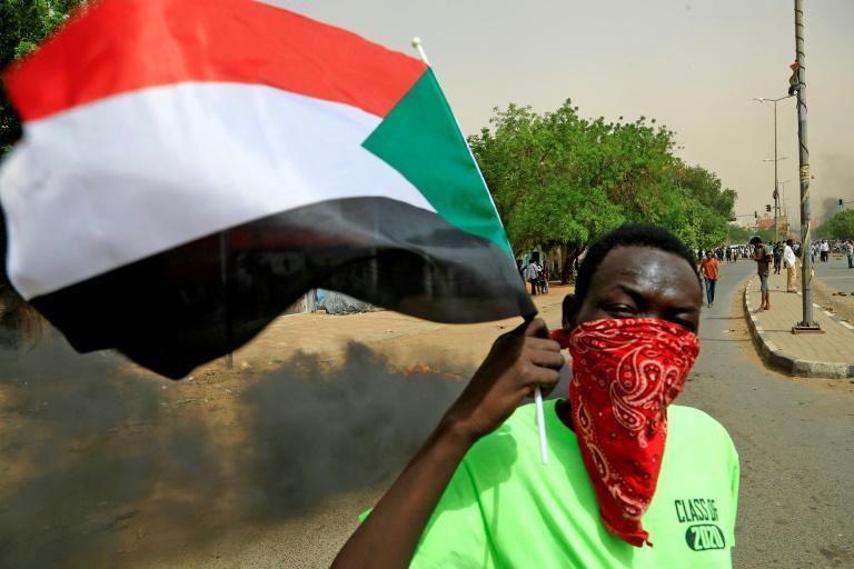 A masked protester waves a flag during a demonstration in Khartoum calling for the Sudanese government to resign over IMF-backed reforms