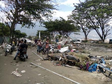 Resident checks dead bodies to find their family at a street after tsunami hit in Palu, Indonesia September 29, 2018. REUTERS/Stringer