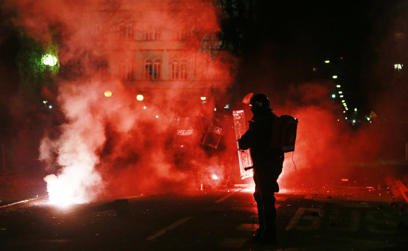 A riot police officer is silhouetted against flares during clashes between police and anti government protestors in Maribor, Slovenia, Monday, Dec. 3, 2012. Anti government protests were held throughout Slovenia the day after presidential elections (AP Photo/Darko Bandic)