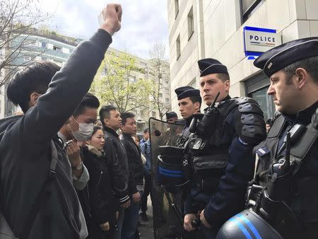 French police face off with members of the Chinese community during a protest demonstration outside a police station in Paris