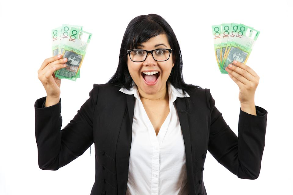 A businesswoman with both hands full of Australian one hundred dollar notes. Studio shot on a white background.