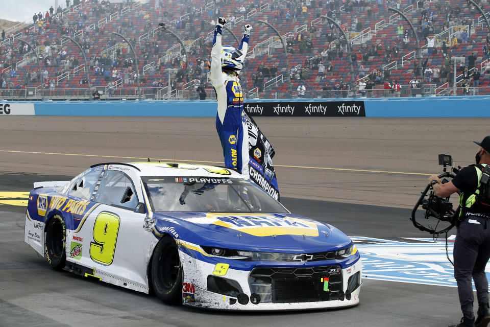 Chase Elliott stands on his race car to acknowledge the fans after winning the season championship and the NASCAR Cup Series auto race at Phoenix Raceway, Sunday, Nov. 8, 2020, in Avondale, Ariz. (AP Photo/Ralph Freso)
