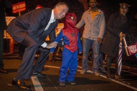 Democratic New York City mayoral candidate Bill de Blasio poses with a child dressed as Spiderman during the Park Slope Halloween Parade in New York