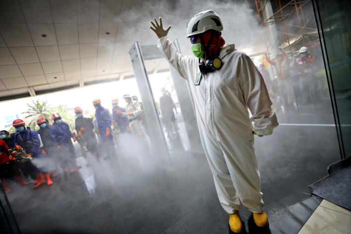 A team leader makes a hand signal as Indonesian firemen test their equipment prior to disinfecting Margo City shopping mall to help curb the spread of the new coronavirus outbreak, after a number of employees of a supermarket at the mall were tested positive for the virus, in Depok, Indonesia, Saturday, Aug. 22, 2020. (AP Photo/Dita Alangkara)