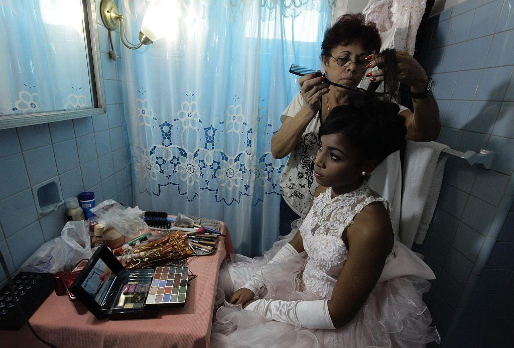 <p>Carmen Gonzalez has her hair done during a photo session for her quinceanera.</p>