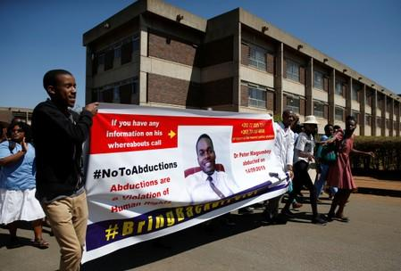 Striking healthcare workers march to protest over the disappearance of Peter Magombeyi, the leader of their union, outside a hospital in Harare