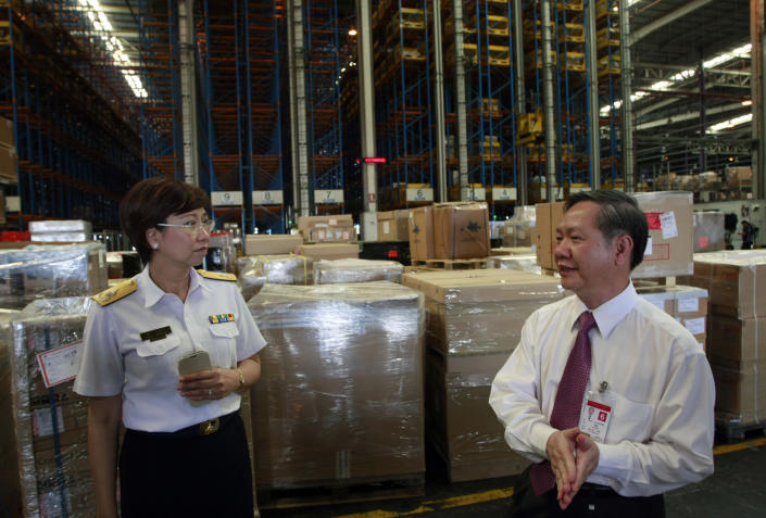 In this photo taken July 17, 2012, Cargo Custom office Director Chalida Phungravee, left, talks with her staff at a cargo warehouse at Suvarhabhumi International Airport in Bangkok, Thailand. Officials at Thailand's gateway airport proudly tick off the illegally trafficked wildlife they have seized over the past two years. But Thai and foreign law enforcement officers tell another story: officials working-hand-in-hand with the traffickers ensure that other shipments through the airport are whisked off before they even reach customs inspection. (AP Photo/Apichart Weerawong)