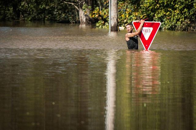 <p>A man holds onto a yield sign after trying to swim out to help a stranded truck driver at NC 301 Highway and Tom Starling Road in Hope Mills, N.C., on Sunday, Oct. 9, 2016. Both people were rescued. (Photo: Andrew Craft/The Fayetteville Observer via AP) </p>