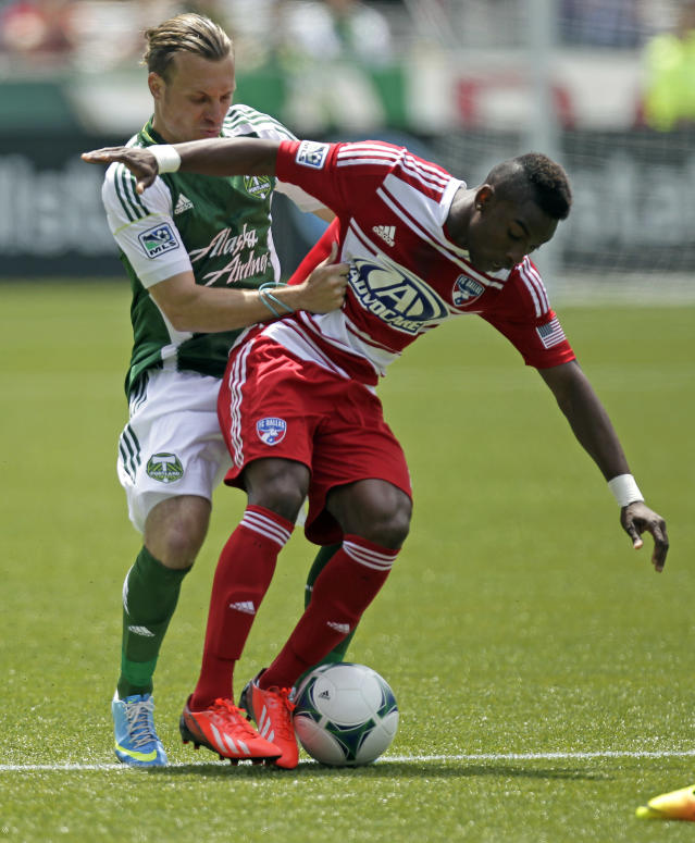 FC Dallas midfielder Fabian Castillo, right, holds off Portland Timbers defender Michael Harrington during the first half of an MLS soccer game in Portland, Ore., Saturday, June 15, 2013. (AP Photo/Don Ryan)