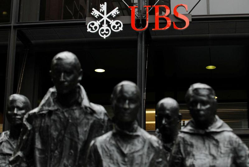 FILE PHOTO: Statues stand in front of the London office of Swiss bank UBS in London