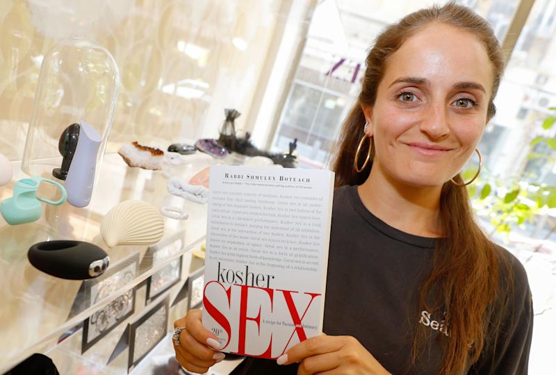 "EDITORS NOTE: Graphic content / Chana Boteach, daughter of Rabbi Shmuley Boteach, poses for a picture with her father's book on kosher sex, in her sex shop in the center of the Israeli coastal city of Tel Aviv, on August 30, 2019. - Behind what seems to be a nice clothing shop, the Rabbi's daughter sells sex toys and books about sexuality. With her father, they hope to open crowds to ""Kosher Sex"": Sexual pleasure within the rules of Judaism. (Photo by JACK GUEZ / AFP) (Photo credit should read JACK GUEZ/AFP/Getty Images)"