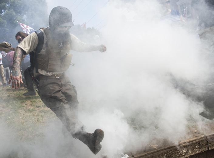 <p>A White Supremacist kicks back a smoke bomb thrown by counter protestors during clashes at Emancipation Park where the White Nationalists are protesting the removal of the Robert E. Lee monument in Charlottesville, Va., on Aug. 12, 2017. (Photo: Samuel Corum/Anadolu Agency/Getty Images) </p>