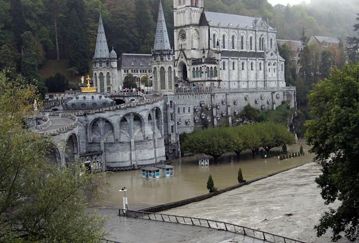 A guardian of Lourdes sanctuary looks the Grotto of Lourdes flooded, in Lourdes, southwestern France, Saturday, Oct.20,2012. French rescue services and police are evacuating hundreds of pilgrims from hotels threatened by floodwaters from a rain-swollen river in the Roman Catholic shrine town of Lourdes. (AP Photo/Bob Edme)