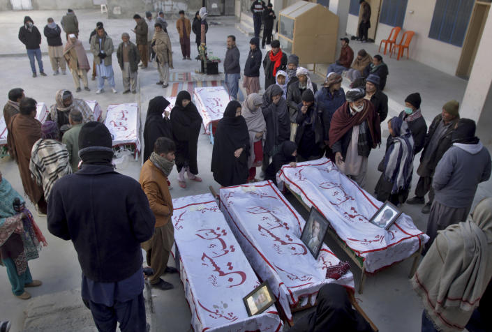 People from the Shiite Hazara community mourn beside the coffins of coal mine workers who were killed by gunmen near the Machh coal field prior to their funeral prayer in Quetta, Pakistan, Saturday, Jan. 9, 2021. Hundreds of Pakistani Shiites gathered to bury 11 coal miners from the minority Hazara community who were killed by the Islamic State group, ending over a week of protests that sought to highlight the minority community's plight. (AP Photo/Arshad Butt)
