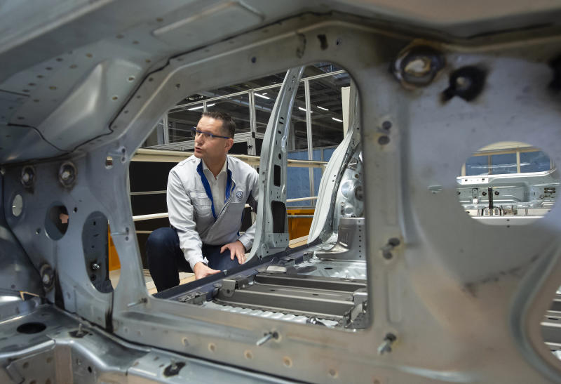 In this Tuesday, May 14, 2019 photo, Heiko Roesch, head of body construction, explains details of the new electric 'ID.3' car body during a press tour at the plant of the German manufacturer Volkswagen AG (VW) in Zwickau, Germany. Volkswagen will total shift into electric cars at the plant in Zwickau and the first vehicles are to roll off the assembly line at the end of 2019. (AP Photo/Jens Meyer)