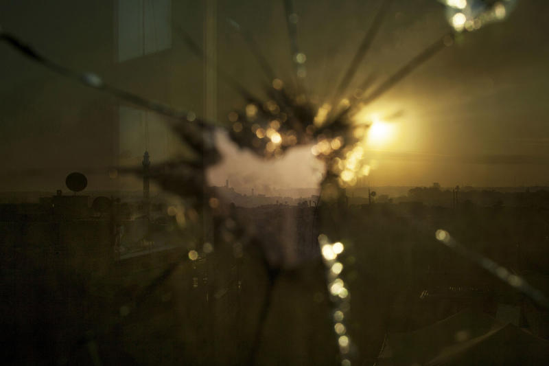 In this Saturday, Oct. 13, 2012 photo, smoke rises from buildings due to government forces shelling seen through broken glass in Aleppo, Syria. (AP Photo/ Manu Brabo)