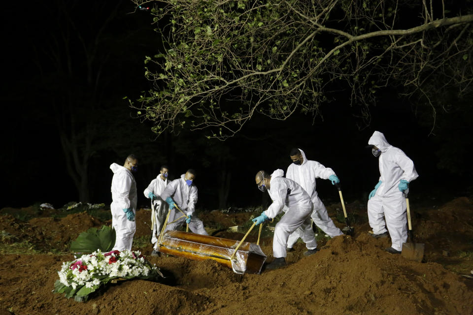 FILE - In this March 31, 2021 file photo, cemetery workers work hours past sundown, as they lower the coffin that contain the remains of a COVID-19 victim into a freshly dug grave at the Vila Formosa cemetery in Sao Paulo, Brazil. Nighttime burials at Vila Formosa and three other cemeteries in Sao Paulo were suspended Wednesday, April 28, after two weeks of declining deaths. (AP Photo/Nelson Antoine, File)