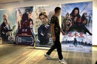 """A man wearing a face mask walks past a poster for the Disney movie """"Mulan"""" at a movie theater in Beijing, on Sept. 11, 2020. The remake of """"Mulan"""" struck all the right chords to be a hit in the key Chinese market. Disney cast beloved actresses Liu Yifei as Mulan and removed a popular dragon sidekick in the original to cater to Chinese tastes. (AP Photo/Mark Schiefelbein)"""