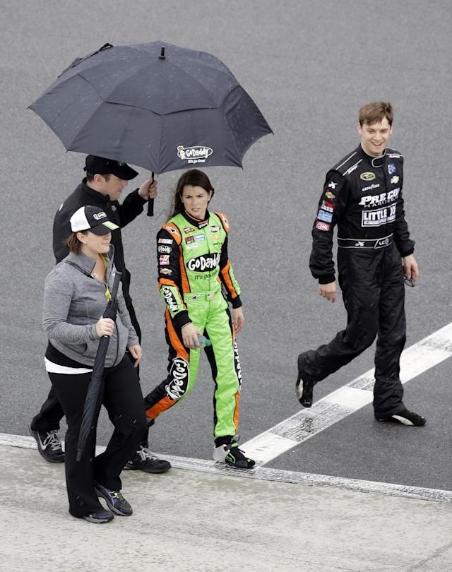 Danica Patrick, second from right, and Landon Cassill, right, walk down pit road during a rain delay in the NASCAR Daytona 500 Sprint Cup series auto race at Daytona International Speedway in Daytona Beach, Fla., Sunday, Feb. 23, 2014. (AP Photo/John Raoux)