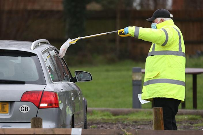 A test and trace worker in the Bramley Inn car park in Bramley, near Basingstoke, Hampshire takes a coronavirus test from a driver at a surge testing programme with local residents, after a case of the South African variant of Covid-19 was identified in the village (PA)