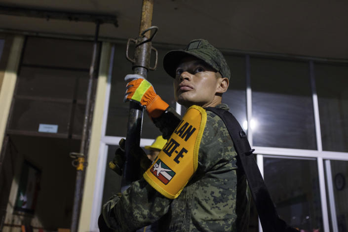 <p>A Marine holds on to a support beam as he waits for the beam to be tightened during rescue efforts at the Enrique Rebsamen school in Mexico City, Thursday, Sept. 21, 2017. (Photo: Anthony Vazquez/AP) </p>