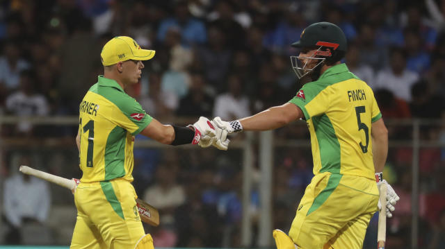 Australia's captain Aaron Finch, right, and David Warner cheer each other as they bat during the first one-day international cricket match between India and Australia in Mumbai, India, Tuesday, Jan. 14, 2020.b(AP Photo/Rafiq Maqbool)