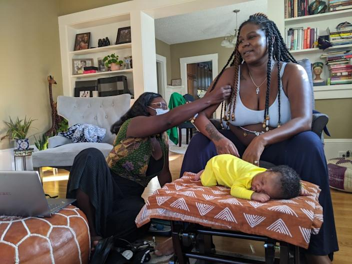 "Midwife Kiki Jordan examines TaNefer Camara during a routine postnatal visit about a week after the birth of her son Esangu. In centuries past, Black midwives often functioned as spiritual advisers and parenting teachers as well as birth attendants. <span class=""copyright"">(Rachel Scheier / California Healthline)</span>"
