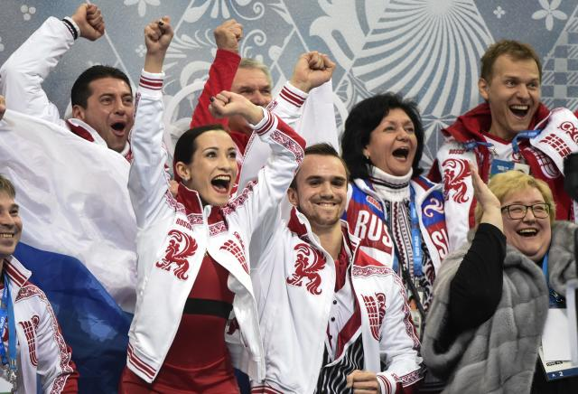Kseria Stolbova and Fedor Klmovper from Russia along with team members react as their marks are posted for their free program in the pairs event of the figure skating team event at the Iceberg Skating Palace during the 2014 Winter Olympics, Saturday, Feb. 8, 2014, in Sochi, Russia. (AP Photo/The Canadian Press, Paul Chiasson)