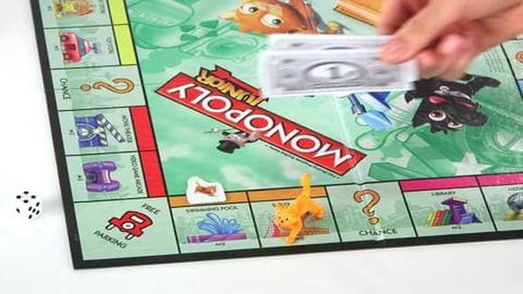 A Monopoly board with a number of pieces on it