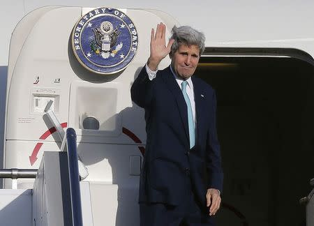 U.S. Secretary of State John Kerry waves as he steps aboard his aircraft in Sydney