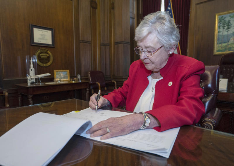 This photograph released by the state shows Alabama Gov. Kay Ivey signing a bill that virtually outlaws abortion in the state on Wednesday, May 15, 2019, in Montgomery, Ala. Republicans who support the measure hope challenges to the law will be used by conservative justices on the U.S. Supreme Court to overturn the Roe v. Wade decision which legalized abortion nationwide. (Hal Yeager/Alabama Governor's Office via AP)
