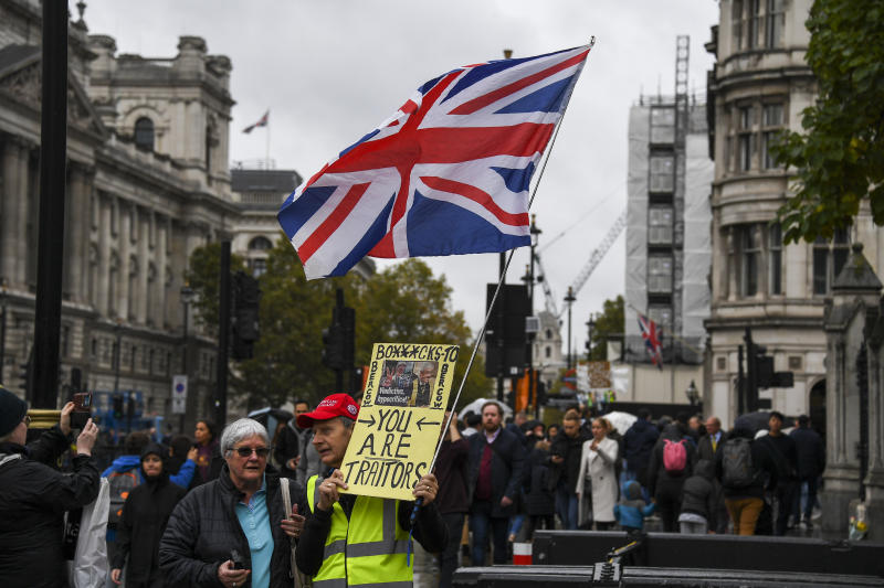 A pro Brexit demonstrator protests outside the Houses of Parliament, holding a placard and a Union flag, in London, Monday, Oct. 21, 2019.  The European Commission says the fact that British Prime Minister Boris Johnson did not sign a letter requesting a three-month extension of the Brexit deadline has no impact on whether it is valid and that the European Union is considering the request. (AP Photo/Alberto Pezzali)