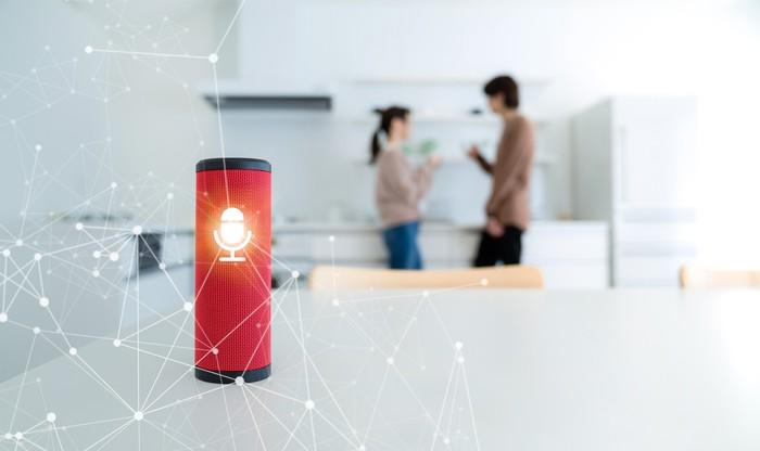 A smart speaker on a table with a couple in the background.