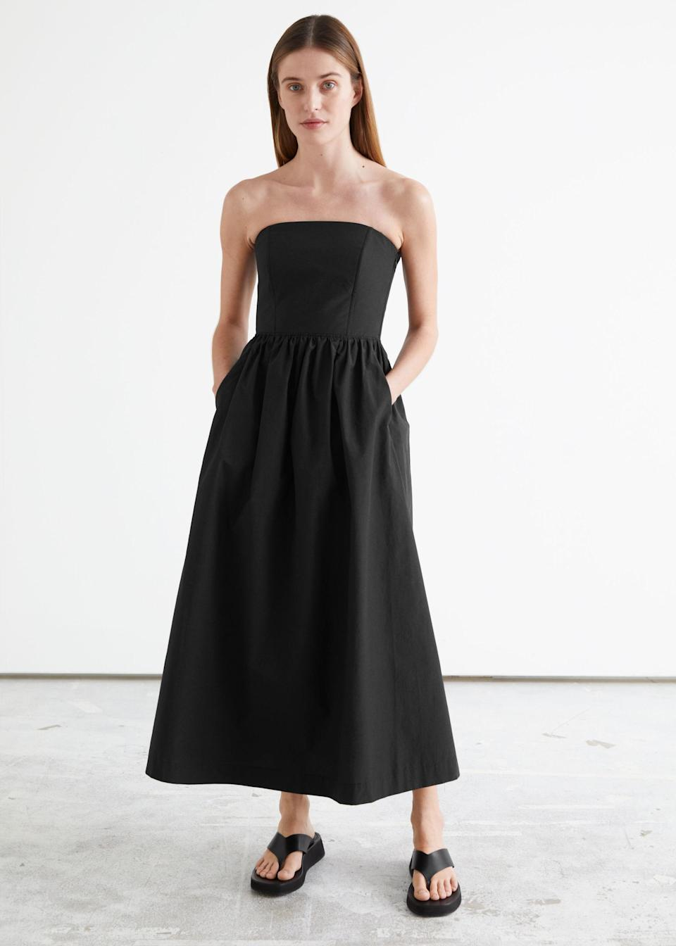 """We stan a bridesmaid's dress with pockets—especially when it's only $129. $129, & Other Stories. <a href=""""https://www.stories.com/en_usd/clothing/dresses/midi-dresses/product.voluminous-bandeau-midi-dress-black.0961926001.html"""" rel=""""nofollow noopener"""" target=""""_blank"""" data-ylk=""""slk:Get it now!"""" class=""""link rapid-noclick-resp"""">Get it now!</a>"""