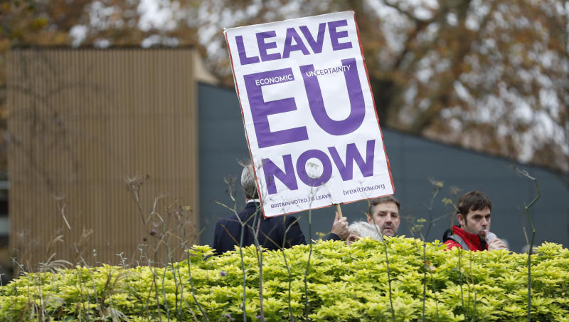 Pro Brexit protesters hold placards trying to get media attention near Parliament in London, Friday, Nov. 16, 2018. Britain's Prime Minister May still faces the threat of a no-confidence vote, after several Conservative Party lawmakers said they had written letters asking for one. (AP Photo/Alastair Grant)