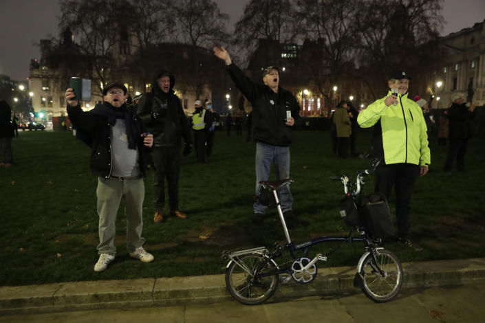 People raise a glass and celebrate in Parliament Square as the bell known as Big Ben strikes 2300, and Britain ends its transition period and formally leaves the European Union in London, Thursday, Dec. 31, 2020. Due to the coronavirus pandemic and the restrictions on gatherings people were moved on by police if they met in any number. (AP Photo/Matt Dunham)