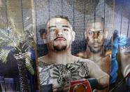 """In this Saturday, Dec. 14, 2019 photo, Visitors of Diriyah a touristic site, in Riyadh, Saudi Arabia are seen through a banner showing famous boxers Andy Ruiz Jr., left, and Britain's Anthony Joshua who played in Riyadh earlier in December. """"Sports has been a tool for social change within the kingdom"""", Prince Abdulaziz bin Turki al-Faisal, who leads the General Sports Authority, said during an interview with the Associated Press. (AP Photo/Amr Nabil)"""