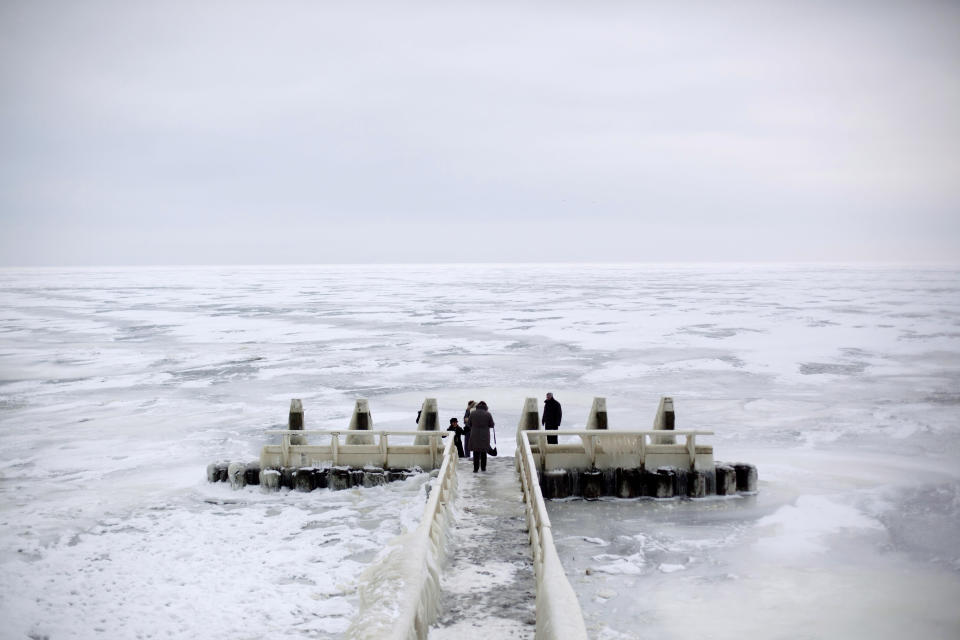 In this image taken Thursday Feb. 9, 2012, Tourists admire the frozen IJsselmeer inland sea on Afsluitdijk, a dike closing off the Wadden sea and North Sea from IJsselmeer inland sea, northern Netherlands. Rising in a thin line through the surface of waters separating the provinces of North Holland and Friesland, the 87-year-old Afsluitdijk is one of the low-lying Netherlands' key defenses against the sea. With climate change bringing more powerful storms and rising sea levels, it's getting a major makeover. (AP Photo/Peter Dejong)