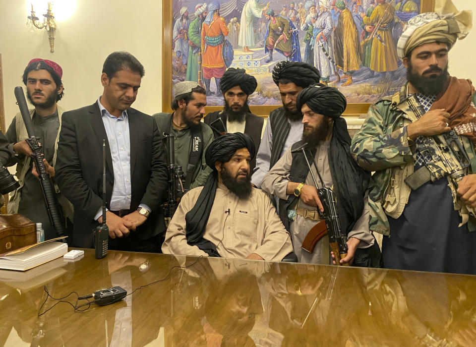 Taliban fighters take control of the Afghan presidential palace after Afghan President Ashraf Ghani fled the country, in Kabul, Afghanistan, Sunday, Aug. 15, 2021. Person second from left is a former bodyguard for Ghani. (Zabi Karimi/AP Photo)