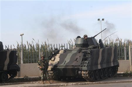 Lebanese army soldiers stand by a tank while monitoring a street in Tripoli