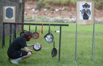 A man checks his aim on the makeshift targets frying pans at a shooting range in Americana, in the Sao Paulo state of Brazil, Saturday, March 6, 2021. Anti-gun activists, a former defense minister and high-ranked former policemen are appalled by the loosening of gun restrictions, saying allowing more weapons into Brazil will only invite more mayhem. (AP Photo/Andre Penner)