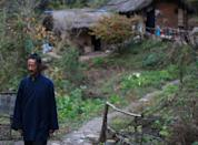 Master Hou walks near his cottage in the Zhongnan mountains, north China's Shaanxi province, October 31, 2014