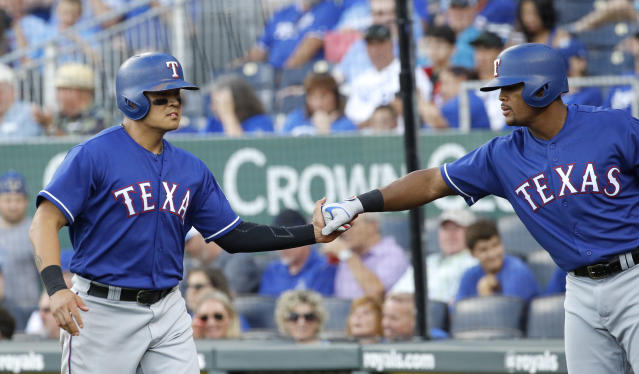 Texas Rangers' Shin-Soo Choo, left, celebrates with Adrian Beltre after Choo scored on a sacrifice fly by Nomar Mazara during the first inning of a baseball game against the Kansas City Royals on Wednesday, June 20, 2018, in Kansas City, Mo. (AP Photo/Charlie Riedel)