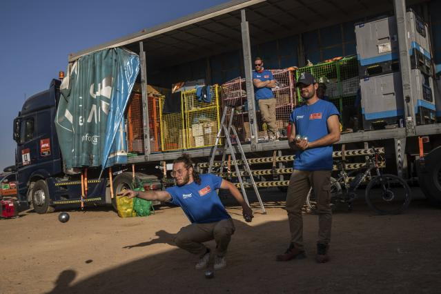 In this Monday, Jan. 13, 2020 photo, Dakar rally staffers play petanque after stage eight in Wadi Al Dawasir, Saudi Arabia. Formerly known as the Paris-Dakar Rally, the race was created by Thierry Sabine after he got lost in the Libyan desert in 1977. Until 2008, the rallies raced across Africa, but threats in Mauritania led organizers to cancel that year's event and move it to South America. It has now shifted to Saudi Arabia. The race started on Jan. 5 with 560 drivers and co-drivers, some on motorbikes, others in cars or in trucks. Only 41 are taking part in the Original category. (AP Photo/Bernat Armangue)