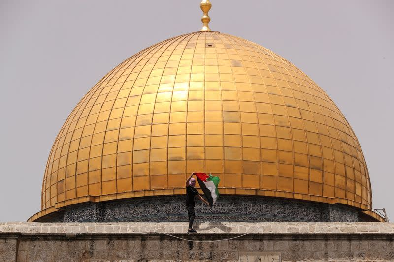 A Palestinian man holds a flag as he stands at the compound that houses Al-Aqsa Mosque in Jerusalem's Old City