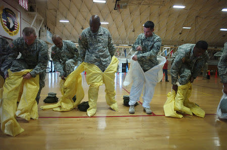 U.S. Army soldiers from the 101st Airborne Division (Air Assault), who are earmarked for the fight against Ebola, put on protective suits during training before their deployment to West Africa, at Fort Campbell, Kentucky October 9, 2014.  REUTERS/Harrison McClary