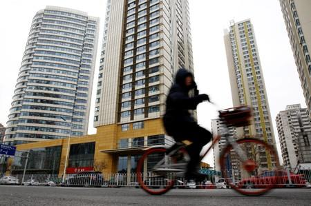 FILE PHOTO: Woman cycles past a building where the Huaying Haitai Science and Technology Development Co is registered, in Tianjin
